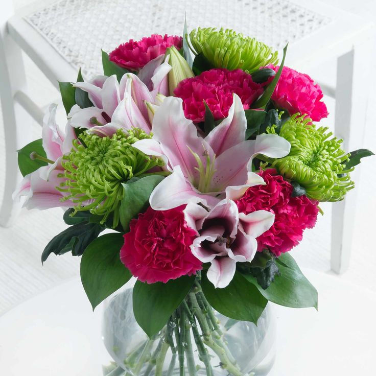 Bloom and Lily - Vibrant green chrysanthemum blooms, pink lilies and cerise carnations come together to make a stunning arrangement that's sure to delight.