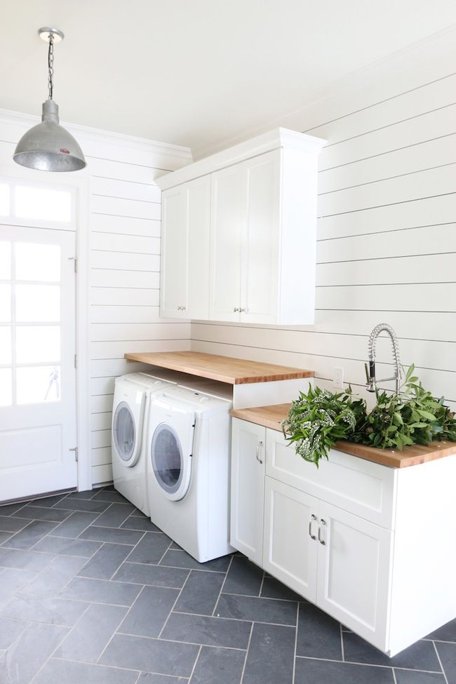 This laundry room uses all white with wood accents to create a minimal yet cozy vibe!
