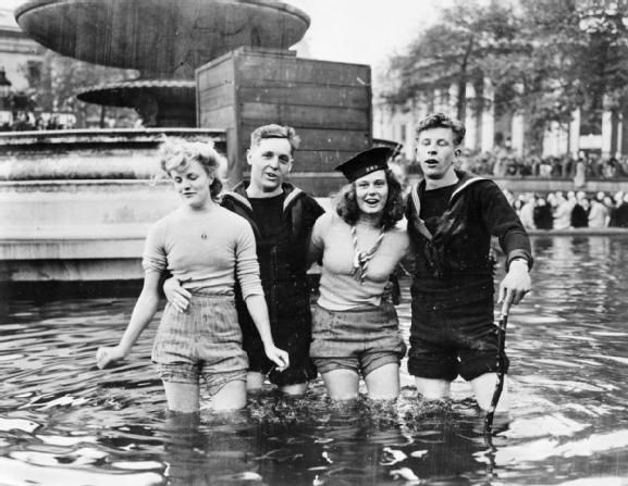 Two British sailors and their girlfriends wading in the fountains in Trafalgar Square on VE Day, 8 MAY 1945.