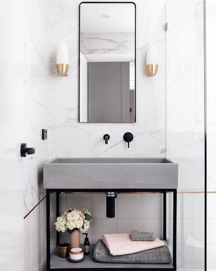 A cuba pré-moldada em concreto é o destaque deste banheiro assinado por Matt and Kim! O volume foi emoldurado e realçado pelo esguio suporte metálico preto, da mesma cor que as torneiras. Foto: Tarina Lyell.