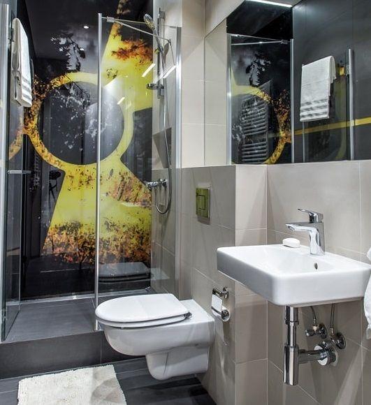 Aranżacja łazienki z prysznicem z odpływem liniowym i szklaną szybą. Prysznic z oryginalną fototapetą na ścianie.