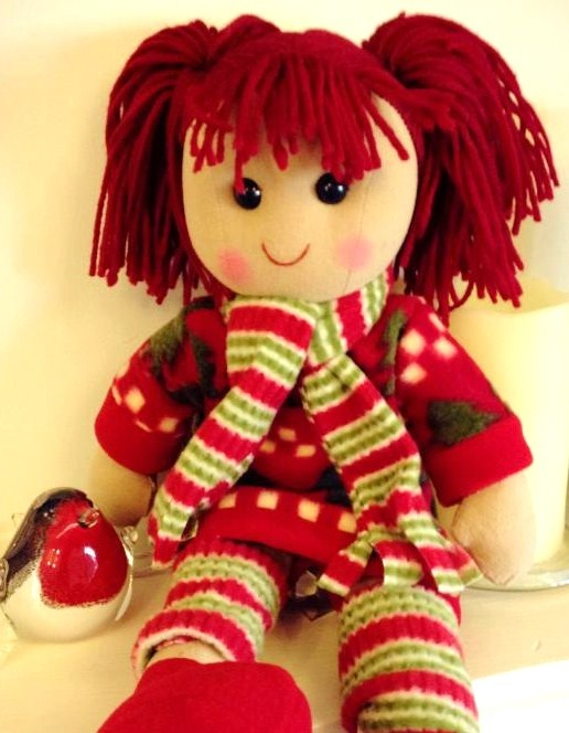 Holly is our very sweet traditional rag doll that has stunning red hair in bunches She is wearing a red and green design dress with matching scarf and leg warmers