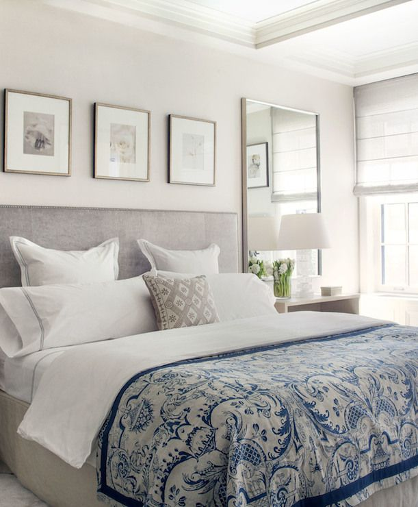 soothing and elegant bedroom, velvet upholstered headboard, linen bed skirt, mirrors over bedside tables, roman shades, coffered ceiling