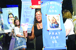 A woman carries a banner in a Marian procession after Mass to mark the Feast of the Assumption at Assumption Grotto Parish in Detroit. For more photos, visit gallery.themichigancatholic.com.