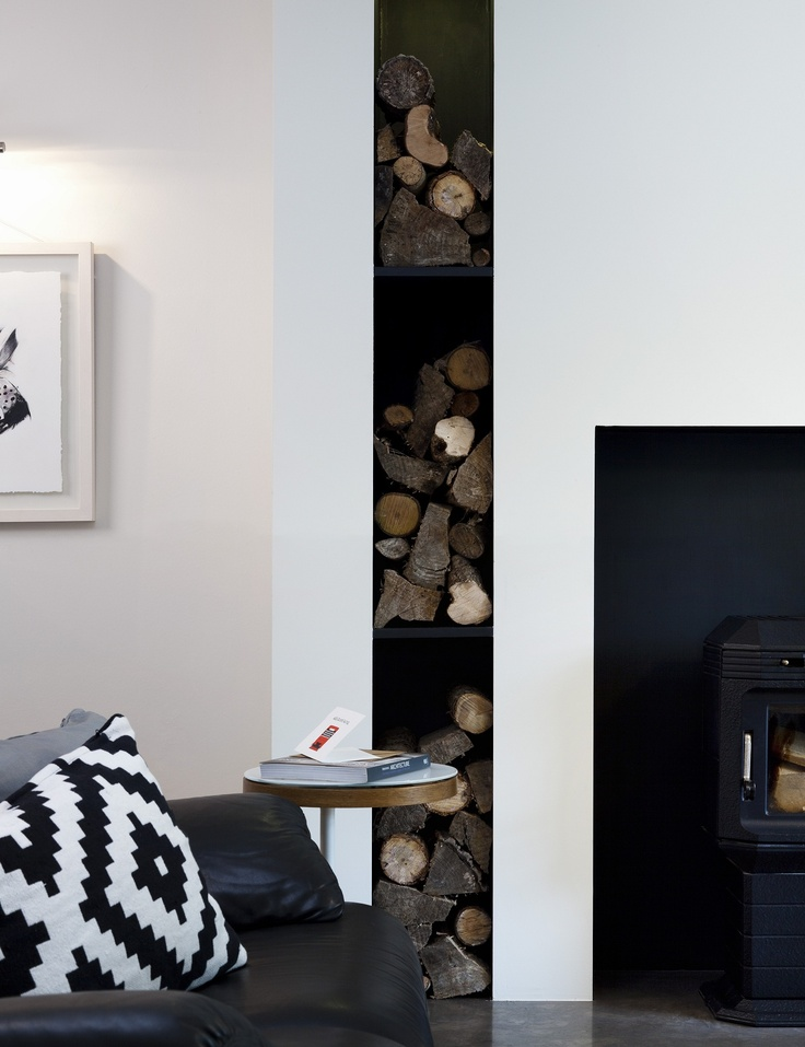 Achitectural fireplace wall with log storage feature area. Mink limestone hearth and blackened steel lined alcoves designed by Kingston Lafferty Design