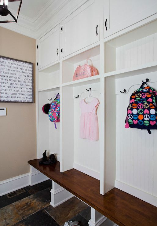 Family friendly mud room with beadboard backed lockers featuring a stained wood bench with coats hooks, cubbies and closet cabinets above alongside camel colored walls adorned with Sugarboo Designs Art Print - Remember When over slated tiled floors.