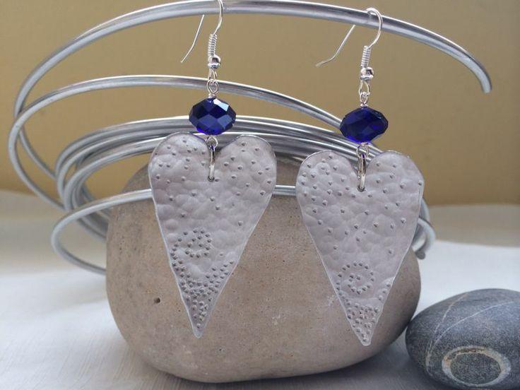 Orecchini in alluminio a forma di cuore realizzati artigianalmente con decorazione a cesello. Abbellitti con un cristallo azzurro!
