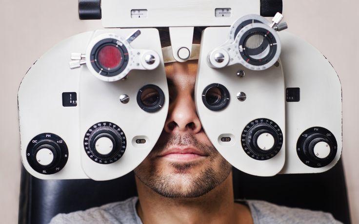 Serious man in phoropter with eye calibration - Man in optometrist phoropter…