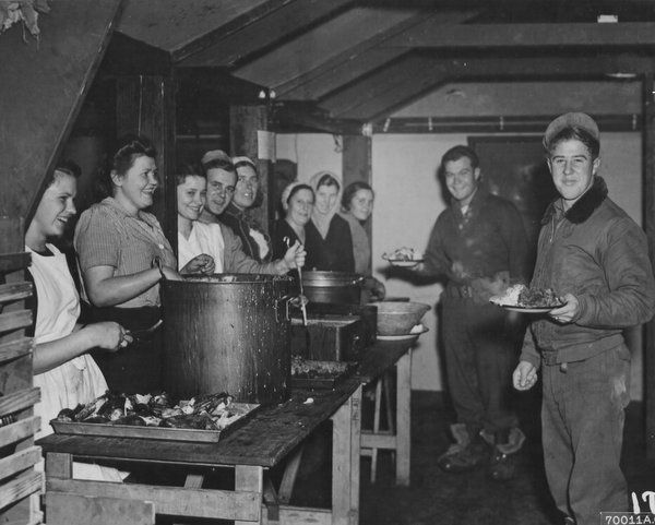 GI's, holding plates heaped with food, grin broadly as they pass thru the chow line in the mess hall at Poltava Airbase, a shuttle bombing base in Russia. The Thanksgiving dinner, served by Russian girls, was the first meal prepared in the newly-opened mess hall. November 1944.