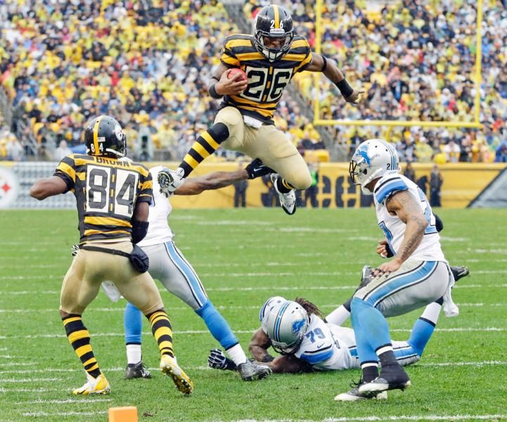 Pittsburgh Steelers running back Le'Veon Bell (26) leaps for more yardage as he tries to evade Detroit Lions strong safety Glover Quin (27) and the defense. (Gene J. Puskar/AP)