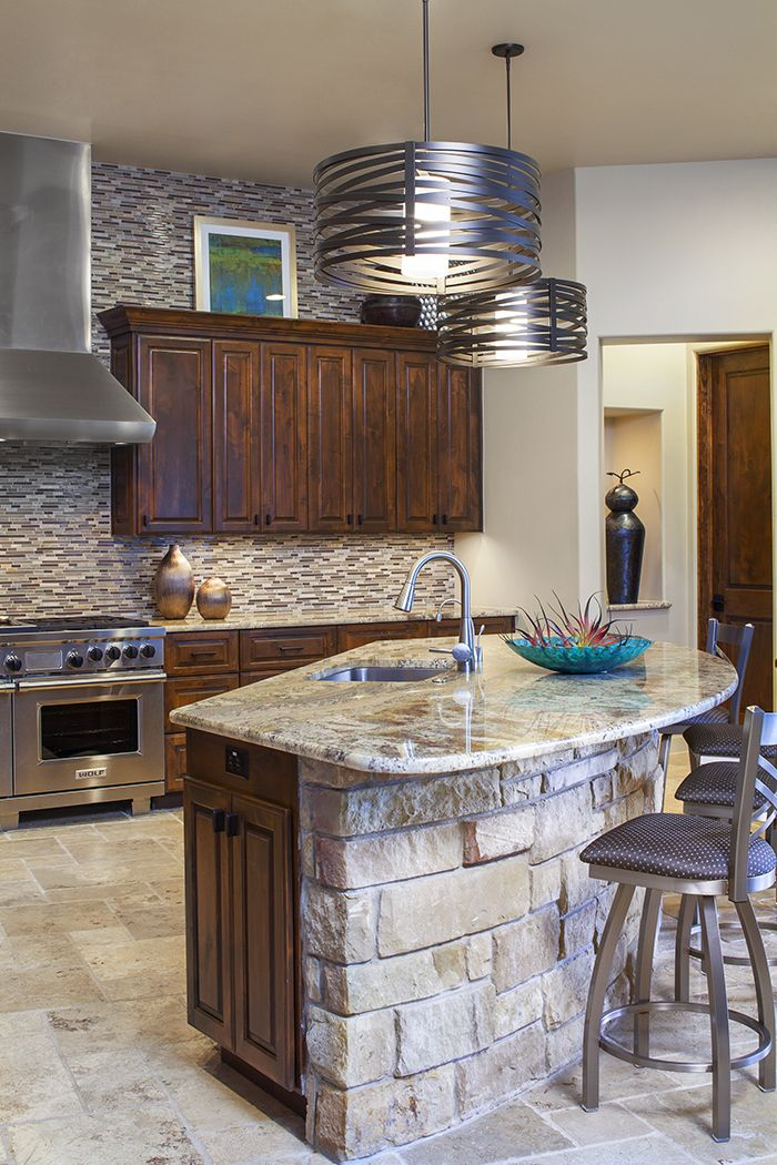A unique curved island with a rock facade and contemporary lighting, stools and tile combine for a warm and textured kitchen.  Austin, Texas Dawn Hearn Interior Design www.dawnhearn.com