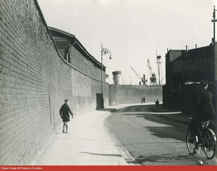 A boy walks beside the Bridge Road high wall, West India Docks. 1934