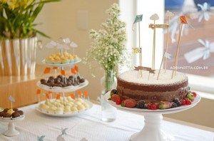 Chá de bebê de menino com tema aviãozinho, barquinho, pipa e cata-vento. Mesa do bolo com tags e topo de bolo de pregador.