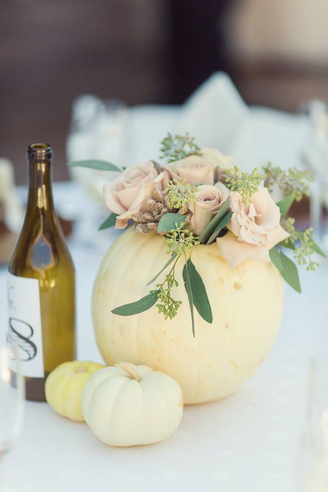 A peach pumpkin centerpiece with pink roses and