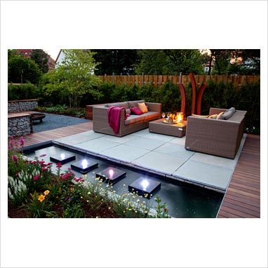 Small garden lit up at night, with wicker sofas on decked and paved patio, backed by Fargesia murielae - Bamboo hedge. Rectangular pond with row of square water features and lights @Dalani Home & Living UK