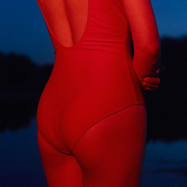 The red colored female body against a dark blue background.