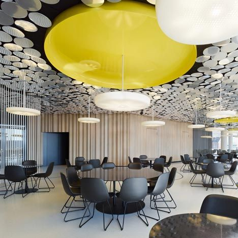 Circular mirrors, glowing acrylic rods and large yellows discs adorn the ceiling of this canteen for German magazine Der Spiegel (photos by Zooey Braun)