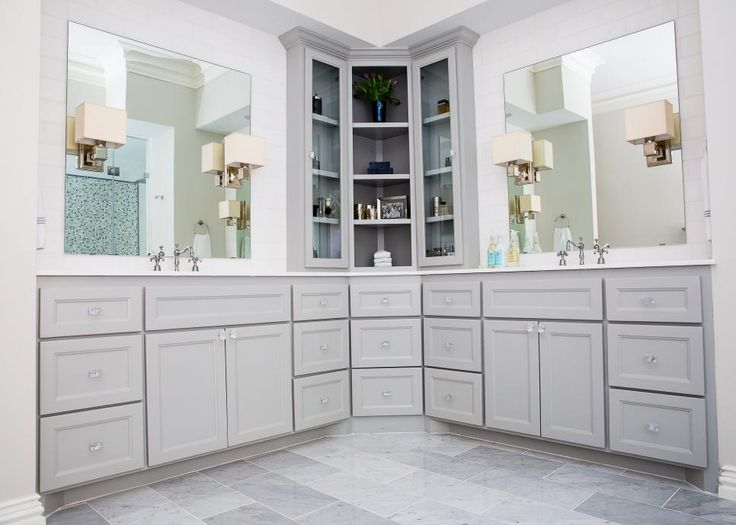 This remodeled bathroom features custom cabinetry with a tall corner unit for added, open storage. Sheet mirrors are backed by sleek white subway tile, with mirror-mounted sconces to provide task lighting. Glass hardware on the doors and draws adds glamour and sparkle.