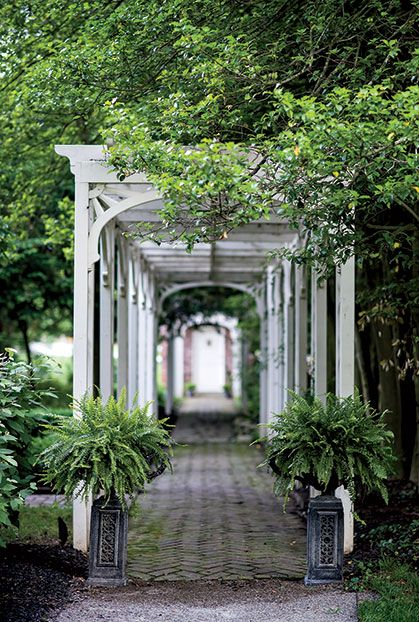 Photo Credit: Andrew Hyslop . The rose-covered pergola and gardener's cottage beyond.