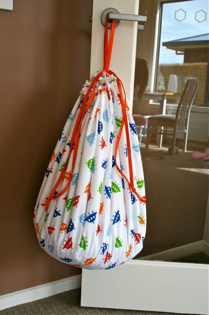 A mat that draws up into a sack to hold Legos, cars, train pieces, etc.! I'm going to make several of these for the playroom in cute coordinating fabrics, then have a peg ledge down low to hang them