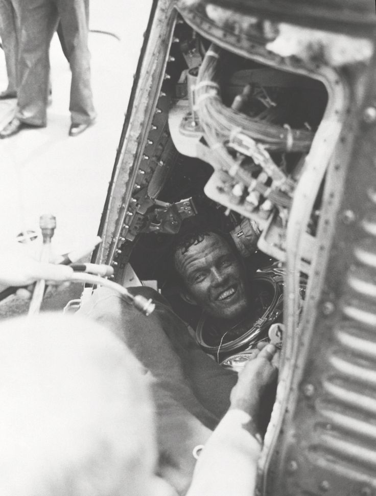 "Astronaut L. Gordon Cooper Jr., has a smile for the recovery crew of the U.S.S. Kearsarge, after he is on board from a successful 22 orbit mission of the Earth in his Mercury spacecraft ""Faith 7."" Cooper is still sitting in his capsule, with his helmet off. (Great Images in NASA)"