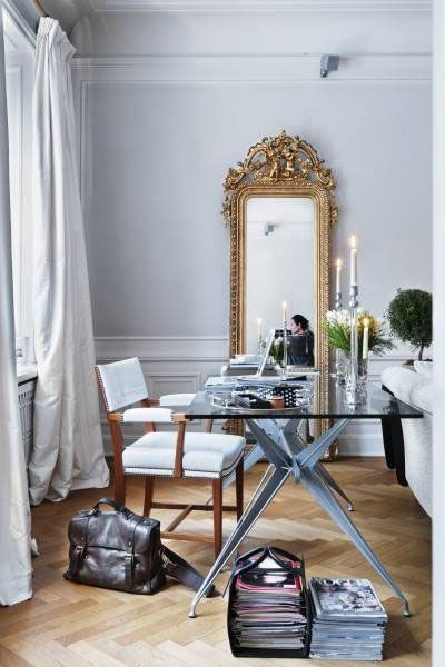 The grand gilt mirror, pools of drapery, and herringbone floors make for a festive and luxurious space.