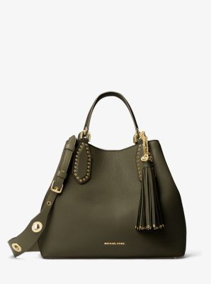 Designed as a go-everywhere style, the Brooklyn tote takes a bohemian turn for the season, thanks to an expansive silhouette and wide shoulder strap with gleaming grommets. An oversized tassel and soft leather craftsmanship give it tactile richness, while the brand's logo offers a refined nod to signature glamour.
