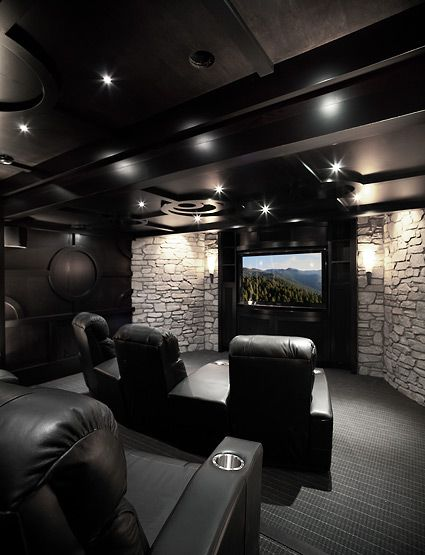 Home theater with rock walls and comfy black seats. www.homecontrols.com