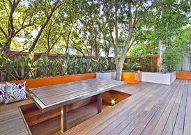 sunken seating with dining table. Rags to Riches Chiswick Roof Terrace Garden Design With Decking, Seating and Lighting