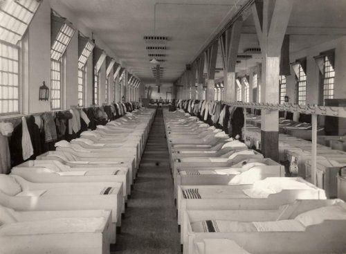 Armenhuis Amsterdam: lange rijen opgemaakte bedden in de slaapzaal van het tehuis aan de Roetersstraat 2. Nederland, 1920