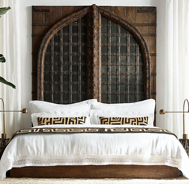 RH's Indian Fortress Bed:A meticulous replica of an 18th-century Indo-Portuguese carriage gate, our bed makes a stunning statement. The dramatic headboard's defining features include a pointed arch and riveted iron strapping, anchored by hand-hammered clavos, or nailheads, that lend rustic appeal. The worn and weathered finish gives it the character of an antique.