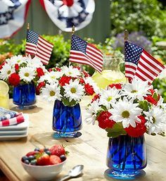 Love this idea - color your water with blue food coloring, add red carnations and white daisies, a flag and VOILA - Patriotic centerpiece th...