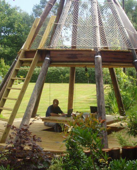 Awesome backyard work/play area! Built by British design gurus Wayne and Geraldine Hemingway, of Red or Dead fame, in Middlesex, UK. The teepee is made from reclaimed wood (including old British Telecom telegraph poles) and features a communal desk on the ground floor with seating set into the decking.