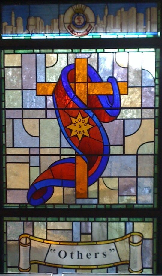 """The bright stained-glass window (detail, above) features the Salvation Army crest against the city skyline, the cross of Jesus Christ wrapped in the Salvation Army flag, and the motto, """"Others,"""" at the bottom."""