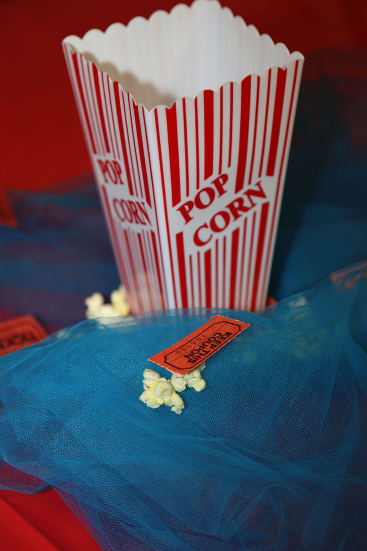 """Vintage Circus Birthday Party by Abbie Pari - we used Popcorn tubs from Target and Dollar Tree as centerpieces for each table. We used aqua blue tulle bunched up underneath each popcorn tub. We added real popcorn and """"admit one"""" tickets (purchased from Dollar Tree) on the table around the popcorn tubs."""