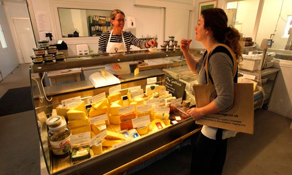 A customer tries a sample from the Highland Dairy cheese counter at Milton of Connage by Ardersier, Highlands