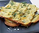 Delikat skivad potatis täckt med smakrik parmesanost, smör, rosmarin och havssalt. Denna ugnsbakade parmesanpotatis kan du servera till kallskuren rostbiff eller en stekt köttbit och en enkel tomatsallad.