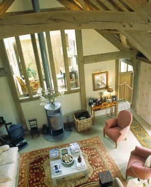 Interior view showing green oak frame and contemporary stove inside Granite House in Dartmoor National Park