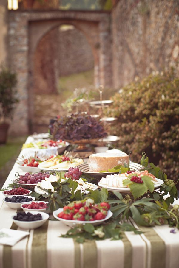 A beautiful Tuscany (?) buffet table with fruit and a huge wheel of cheese :) I love the stonework in the back.