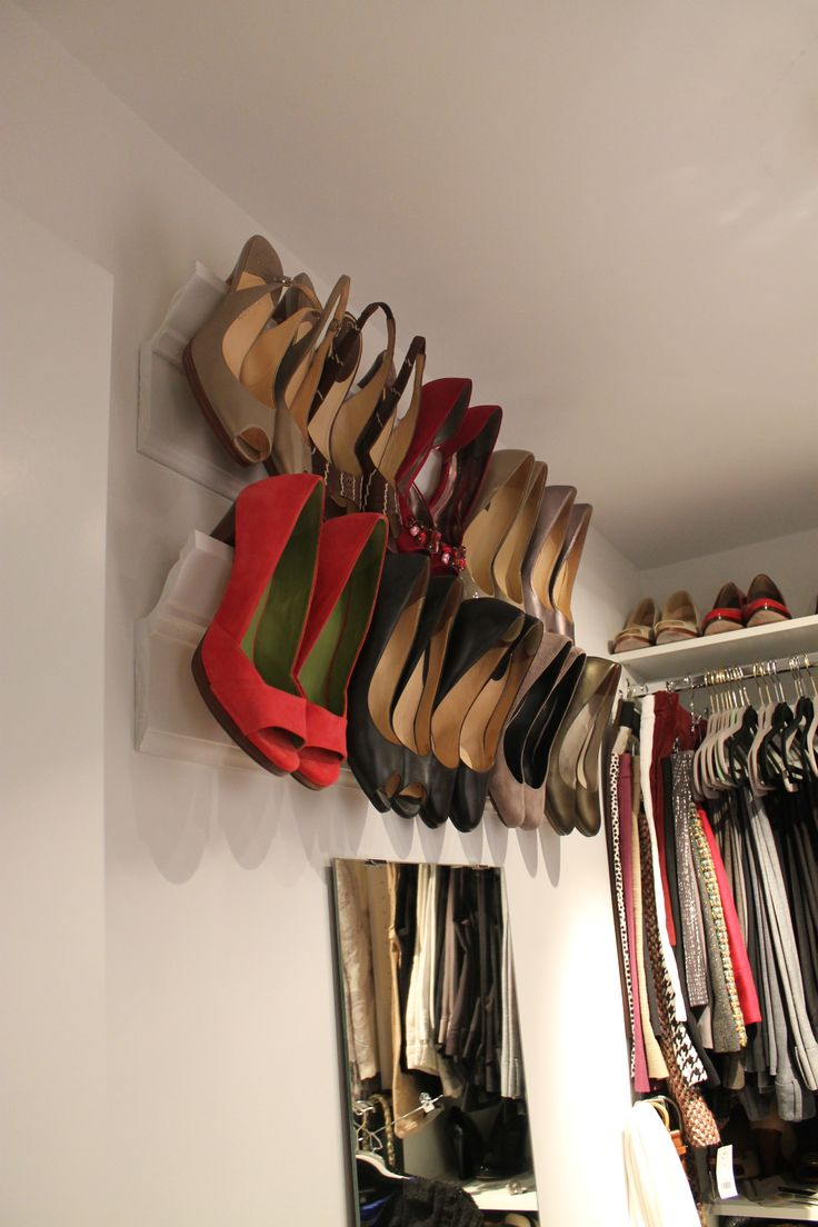 Crown Molding Shoe Shelves- perfect space saver storage.    Total Cost $20  $8- 8' base pine base molding and $9- 8' crown molding + white spray paint.  Wood glue crown on to base molding, finish nail to hold in place while drying, spray paint, install w/ 2 screws onto wall studs. Viola!