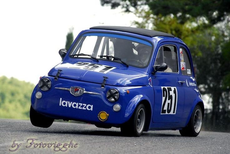 Old abarth 695 in historic hillclimb, with two wheels raised.