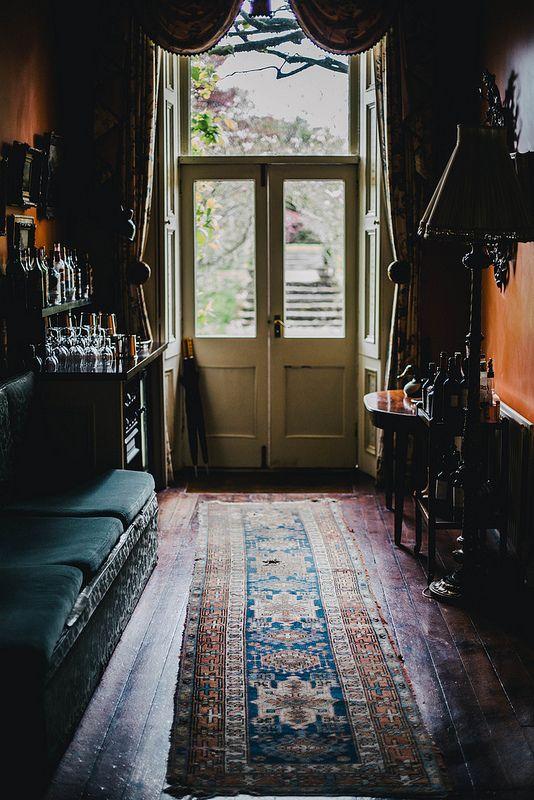 Dark foyer with runner area rug and glass doors via Local Milk | ireland part 2: ballyvolane house