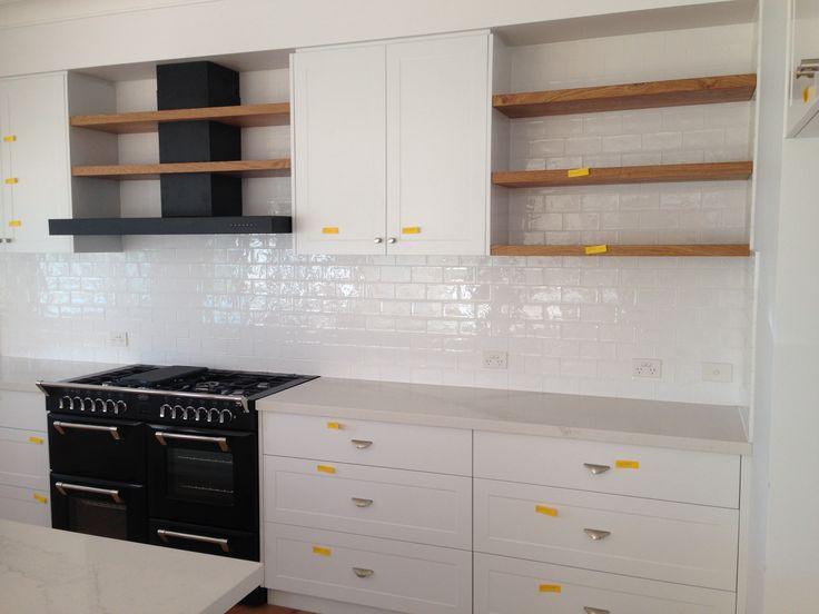 Kitchen:matt black rangehood to black cooker/stove, white subway splashback, floating timber shelving