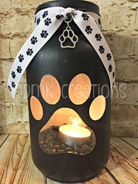 Paw print painted mason jar tea light candle holder 7 inches tall 32 oz painted mason jar. (quart size) Color in photos are black & beige. We have a variety of colors to choose from. Pick your color from drop down menu at checkout. Comes with Ribbon ,charm, tea light candle and beans. ( ribbon maybe different from picture. Depends on what is available) **You can have the jar personalized for $1.00. Message me before purchase of what you want and Ill make a listing for you** If you...