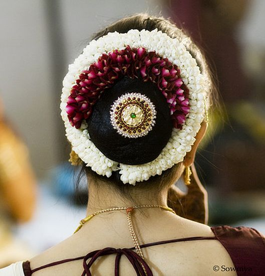 gorgeous low bun with gajra & juda pin. Care however should be taken before adopting such hairstyles, as due to it's high static charge, it will cause phlegm to move up in the throat, causing the voice to quaver & a frequent urge to clear the throat. A heavy chabi chhalla with a long & wide hook if inserted at the edge of the pleats of the saree, will reduce this problem as it's hook will activate the acupressure points that act to keep the throat clear.