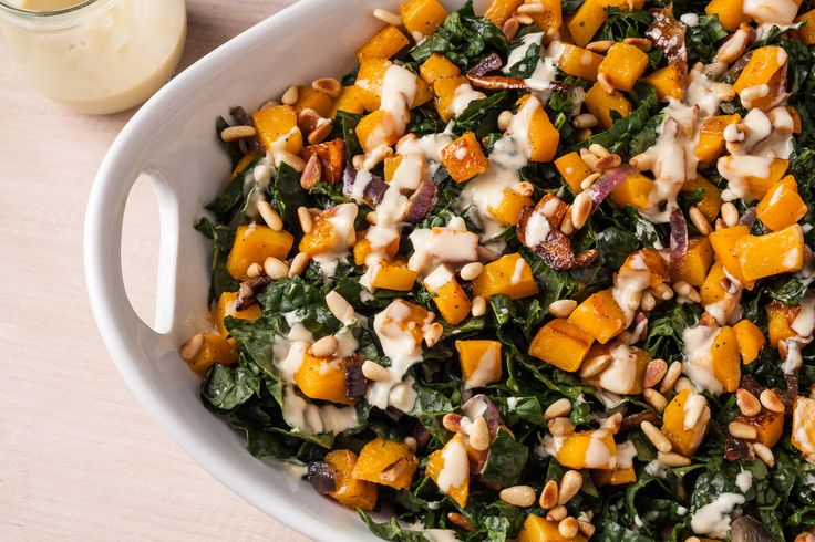 A healthy vegetarian salad recipe with roasted butternut squash, kale, red onion, and pine nuts with tahini dressing.