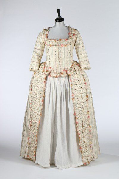 A rare brocaded silk robe à la Piémontaise, 1770s, the silk woven with delicate foliate stripes, the bodice with tabbed front hem, trimmed in tufted pink, brown, green and gold fly braid, with padded, ruched bands to the front skirt openings, pleated drape falling desending over the fourreau back and culminating in polonaised skirt drapes, two silk covered buttons to the rear waist, bust approx 92cm, 36in
