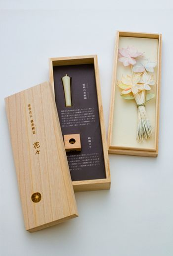 線香花火の持ち手部分が花びらに。それを束ねて「花」を表現しています。保存するのに最適な桐箱入り。ハゼの実から抽出されたロウでできた和蝋燭と、九州の山桜でつくったロウソク立てが付属しています。