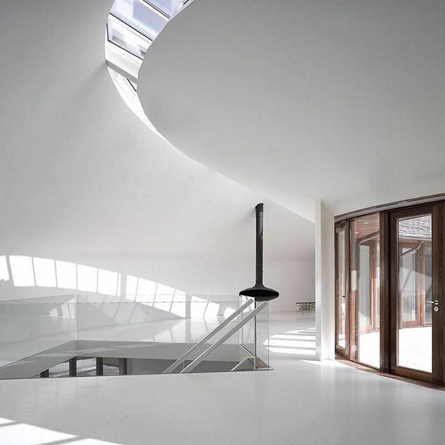 The double-curved Villa Meindersma by Cie Architecture is a harmonious and flawlessly realized ethereal environment. The outer façade, which is comprised, of rough, natural materials and clear wood features no windows. Instead light streams in from alternate sources including the fully glazed inner façade, which encloses the round patio and terrace, along with the frameless strip windows lining the floor and roof. #CernoInspiration #VillaMeindersma #CieArchitecture