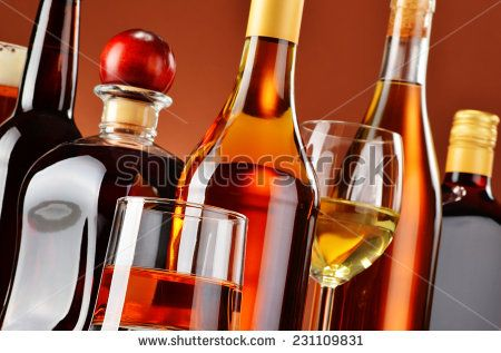 Bottles and glasses of assorted alcoholic beverages. - stock photo